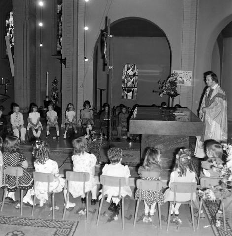 1237_006_251-1_007 - Eerste heilige communie in de Margarita Maria Alacoquekerk. Viering door kapelaan Mennen in mei 1974.   Religie. Kerk. Parochie Ringbaan West.