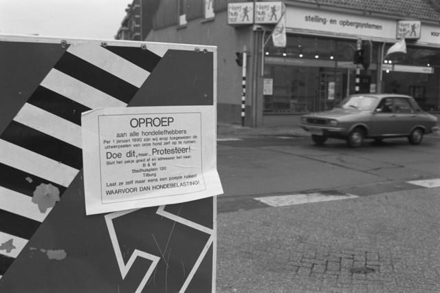 TLB023002709_002 - Oproep tot protest tegen B&W Tilburg mbt poep opruimen / hondebelasting 1990. Geplakt op verkeersbord. De foto is gemaakt aan de Gasthuisring, met op de achtergrond de voormalige winkel van Nico van Helfteren, op de hoek met de Lange Nieuwstraat.
