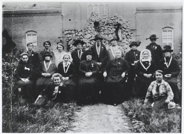 055543 - Religie, Zelatricen van het genootschap van de kindsheid in 1927 op de binnenplaats van het Adrianusgesticht. Zittend op de voorgrond links: Luus Heeren (1901-1979) en rechts Trees barben de Laat (1901-1989). Zittend op de eerste rij v.l.n.r: Miet Verhoeven (1888-1957),  Adriana van den Puijenbroek (1889-1978), Jet Kluijtmans (1855-1941), Maria jacoba Willekes-Kuijpers (1860-1945) ´thesaurriester van de H. Kindsheid´, Pastoor A. van Beijnen, Gonda Jacobs (1859-1942) en Mina van Gestel (1870-1937). Op de laatste rij v.l.n.r: Wil van de Broek, Cor van Oirschot-Blankers (1901-1990), Dina Kluijtmans, Jans de Bruijn (1882-1958), N.N., A. Loots, Mie Elings (1875-1956) en N.N.