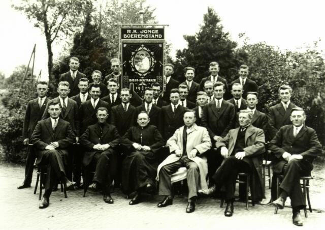054619 - De R.K. Jonge Boerenstand van Biest-Houtakker werd op 9 april 1922 opgericht door J.C. Wijten, H.J. Vriens en J.A. Brekelmans. Op de foto met processievaandel uit circa 1935 zittend v.l.n.r. Piet van de Pas, Piet van Gestel, pastoor Van Hoof, J. Brekelmans, Jan Wijten en P. van Oort. Op de tweede rij v.l.n.r. Jan Kuijpers, Drik v.d. Wouw, Toon v.d. Pas, Jo v.d. Pas, Jan de Graaf, Dré Kuijpers, Nis van Gestel, P. Vriens, Fr. v.d. Sande, H. v.d. Pas, Gerard v.d. Meijdenberg, G. de Brouwer, G. Ketelaars, Toon de Brouwer, Kees van Gestel en Jos van Oirschot. Op de laatste rij v.l.n.r. F. van Beurden, C. v.d. Meijdenberg, R. van Beurden, C. v.d. Sande, Pieter van Gestel, H. van Beurden en Toon van Nuenen.