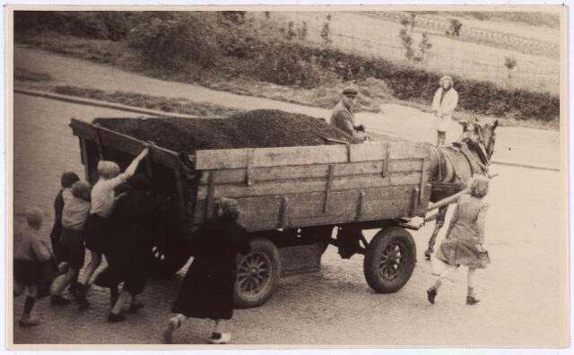 013964 - Tweede Wereldoorlog. Distributie. Brandstof is een schaars goed en als een wagen vol met kolen, bestemd voor gebouwen waarin Duitsers zijn gelegerd, onderweg is, probeert men daarvan een graantje mee te pikken. Vaak worden dergelijke transporten bewaakt door Duitsers, die niet aarzelen om te schieten