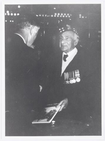 043393 - Op 27 oktober 1984 werden allerlei festiviteiten en herdenkingen gehouden b.g.v. 'Tilburg 40 jaar bevrijd'. In de Heuvelpoort bood Frans Jansse zijn boek 1940-45 via actie van het Stadsnieuws aan Andrew Thornton.