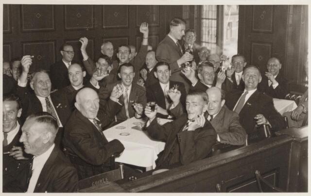 047313 - Installatie van burgemeester G.L. Elsen. Ambtenaren vieren feest op de publieke tribune van het gemeentehuis aan de Kerkstraat. Op de foto staan o.a. de ambtenaren J. van Bergen, H. Vos, A. van Oisterwijk, H. Verkerk, J. Appels, P. van Boxtel, Nooijens, Van Wijk, J. van Rooij, J. van Iersel, H. Hoskes, F. Copal,  W. Koolen, E. Copal, H. van Erven, F. van Gils, F. Hendrikx en F. van Aken.