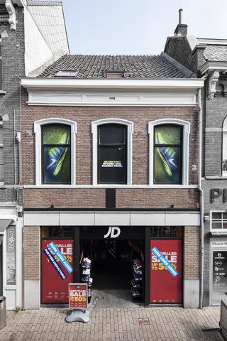 1611_005 - Heuvelstraat in Beeld. Het bovendeel van dit pand oogt nog origineel, beneden is een gat in de gevel opgevuld met veel glas. Vanaf 1965 tot 1975 was Hunkemöller hierin gevestigd, daarvoor de hoeden- en pettenzaak Vervoort en momenteel JD Sports (JD staat voor John Wardle en David Makin).