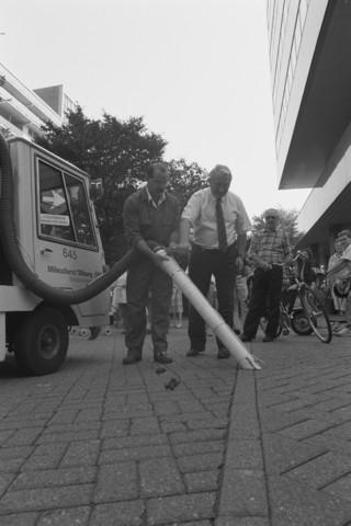 TLB023002704_003 - Milieudienst Tilburg.  Stadsreiniging geeft demonstratie van een hondendrollenzuiger. Publiek kijkt toe.