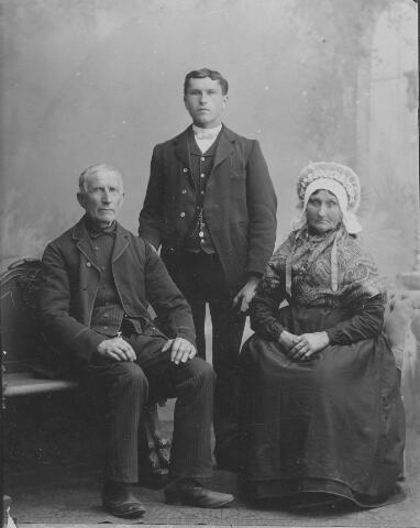 """063977 - Op 6 juni 1867 trouwde te Tilburg klompenmaker Adriaan van Berkel, geboren te Tilburg op 11 juni 1830 als zoon van Johannes van Berkel en Johanna van de Sande, met Petronella Leijten, geboren te Tilburg op 1 november 1824, dochter van Cornelis Leijten en Maria Elisabeth van den Nieuwenhuizen. Het echtpaar Van Berkel-Leijten kreeg slechts een zoon: Johannes Cornelis van Berkel, geboren te Tilburg op 19 september 1871, die, evenals zijn vader, klompenmaker werd. Op de foto Johannes Cornelis van Berkel met zijn ouders. Zijn moeder zou kort daarna, op 22 april 1899, overlijden. Petronella Leijten draagt op de foto een ouderwets type muts met een hoge bol en een lintversiering, de voorloper van de poffer. Het type muts dat zij draagt werd in de volksmond de muts met """"een hekkegat"""" genoemd. Zij draagt een omslagdoek met Kasjmierpatroon en heeft aan bijna ieder vinger een ring."""