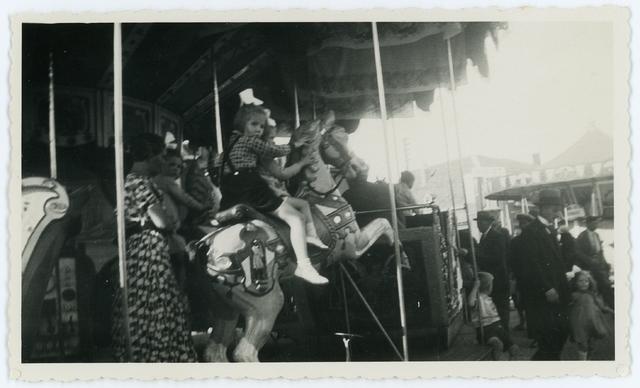 17350012 - Kermis. Zicht op de draaimolen. Meisjes met strikken in het haar zitten op de paarden.