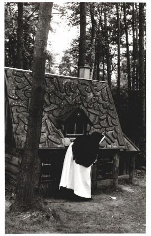 046379 - Medisch kinderdagverblijf Kleuterheil. Een zuster bij het peperkoekhuisje in het bos. Tot 1945 waren de zusters franciscanessen van de H. Familie belast met de leiding van Kleuterheil. Daarna nam een bestuurslid van de stichting de leiding op zich. In 1953 werd dit overgenomen door de zustercongregatie dochters van O.L.V. van het H. Hart.