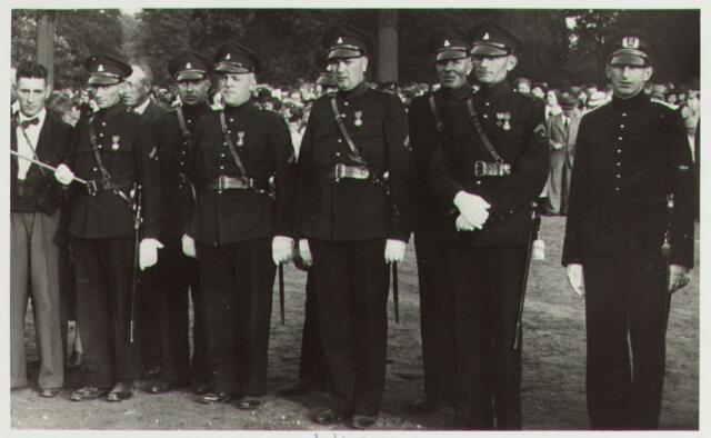 065153 - Politie. Een aantal politiemensen hebben zojuist een onderscheiding ontvangen. Op de achtergrond publiek. Nadere gegevens onbekend.