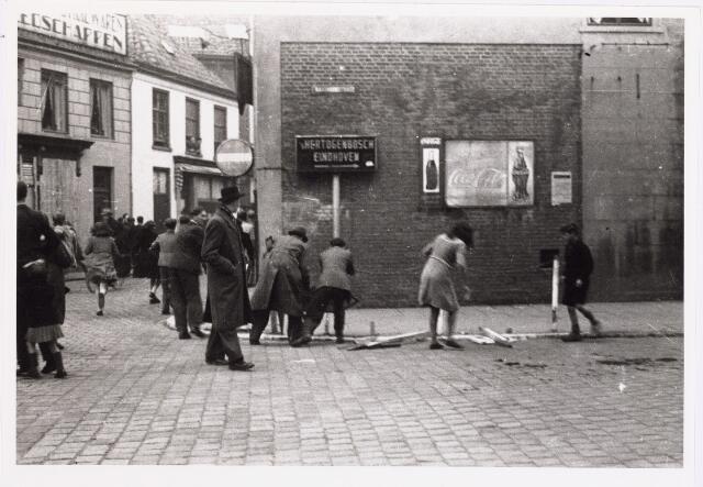 013284 - WO2 ; WOII ; Tweede Wereldoorlog. Bevrijding. De Duitsers waren amper uit de stad verdreven, of de Tilburgse bevolking begon alle herinneringen aan de Duitse bezetting uit het straatbeeld te verwijderen, zoals hier op de hoek Zomerstraat - Raadhuisstraat