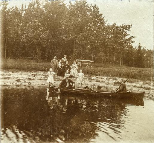653630 - Links in de boot Leon van Dooren, persoon rechts in de boot is onbekend, achter hen staan Muis, Otje en Frits Deelen. De rij daarachter bestaat uit Bernard Sträter, Jo van Dooren-Sträter, oma Sträter-Bahlmann en Agnes Deelen-Sträter. Daarachter weer Dora Sträter. (Origineel is een stereofoto.)