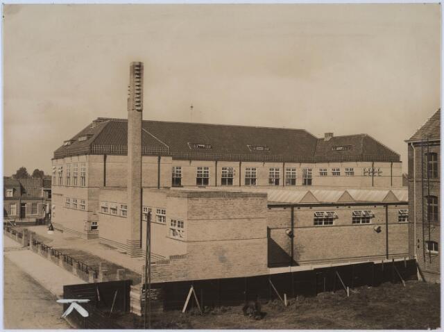 024456 - Textiel. Achterzijde van de textielschool,aan de Noordhoekring 182, gezien vanuit de Korte Schijfstraat. Achter het houten hek ligt het Burgerijpad