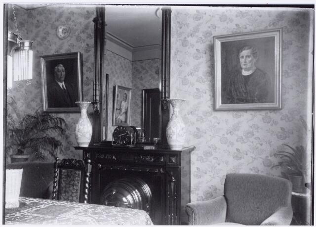 049856 - Foto uit ´Je Taalboek´ van frater Victor van Nispen. Interieur van de huiskamer in een Tilburgse herenhuis. Traditioneel is de kolenhaard met boven de schoorsteen een spiegel. Op de schoorsteenmantel twee vazen en een pendule.
