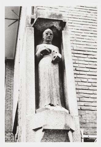 067717 - Beeld van ST. ODULPHUS in de voorgevel van het St. Odulphuslyceum, Noordhoekring 99, naast de inrijpoort. Het beeld is gemaakt door Albert VERSCHUUREN (Tilburg 1887- Oosterhout 1953) en het werd aangeboden door oud-leerlingen van de school, bij gelegenheid van de ingebruikname van het nieuwe gebouw op 20-10-1930. Ook Verschuuren behoorde tot de oud-leerlingen. Materiaal: Brauvilliers (Franse kalksteen). De patroonheilige van de school werd in de 9e eeuw geboren in Oirschot, waar hij enige tijd pastoor was. Later verrichtte hij zendingswerk in Friesland. Hij stichtte een kapittel in Stavoren, reden waarom Odulphus  vaak wordt afgebeeld als kannunnik, een traditie waaraan Verschuuren heeft vastgehouden. De foto dateert uit 1986.  Trefwoorden: Kunst in de openbare ruimte. Onderwijs.