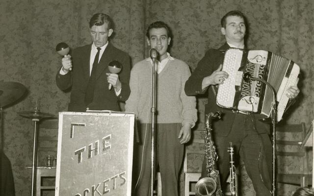 """200028 - """"The Rockets"""", een band uit Poppel was geen rockband, maar speelde voornamelijk """"kermisnummers"""" en dansmuziek. Van links naar rechts: François de Jong, Jantje Brok en Nand de Wit. Nand was slager van beroep, maar zijn vader, Sooi de Wit, bezat een dancing in Poppel. Nand speelde eigenlijk saxofoon en is, nadat """"The Rockets"""" gestopt waren, muzikant geworden bij het """"Enclave Combo"""" uit Baarle-Nassau. Jantje Brok was bij """"The Rockets""""  in feite de accordeonist. Vic de Jong, de trompenist van """"The Rockets"""", staat niet op deze foto."""
