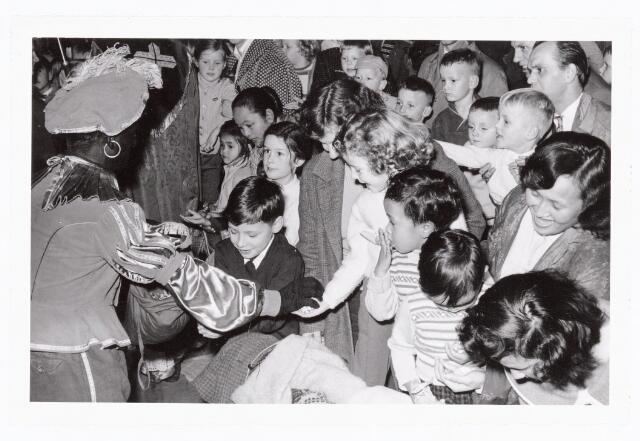 038861 - Volt. Zuid. Sport en ontspanning. Viering Sint Nicolaas voor de kinderen van het personeel in 1960. Zwarte Piet alias Jos Spijkers deelt snoep uit. Sinterklaas. St. Nicolaas