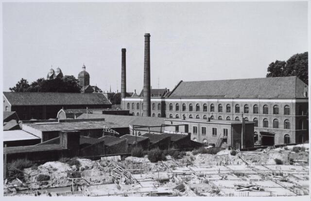 025942 - Fabriek van Van Riel aan de Zomerstraat, thans Louis Bouwmeesterplein, eind september 1959. Op de achtergrond links de St. Annakerk en op de voorgrond de bouw van de Stadsschouwburg.