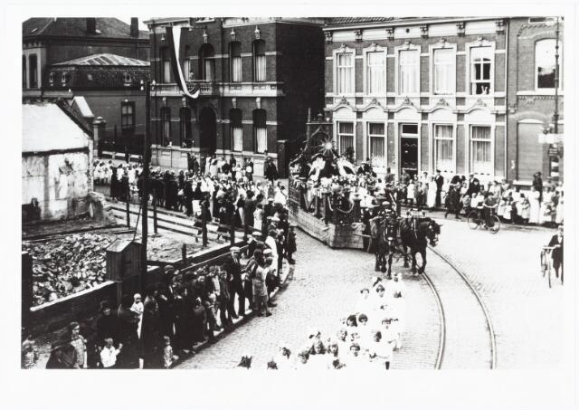 009021 - optocht H. Kindsheid parochie 't Goirke. De optocht draait komende vanaf het Wilhelminapark de  Goirkestraat in. (achter de donkere fabrikantenwoning is nu Museum De Pont gevestigd.