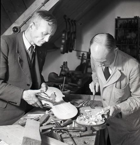 654118 - Middenstand. Rechts Jan van Gorp, vioolbouwer. De man links meet de dikte van het onderblad. Waarschijnlijk is dit de heer Winter.