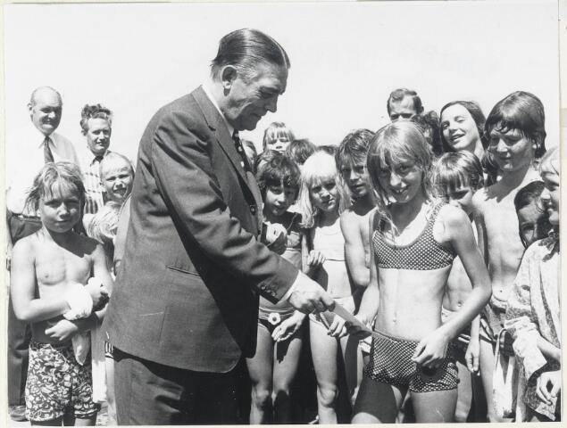 """90932 - Made en Drimmelen. Burgemeester Smits van Made en Drimmelen heet de 100.000ste bezoeker welkom in het zwembad 'De Randoel""""  met een waardebon. Achteraan 2e van links Theo Segers, wethouder van sport."""