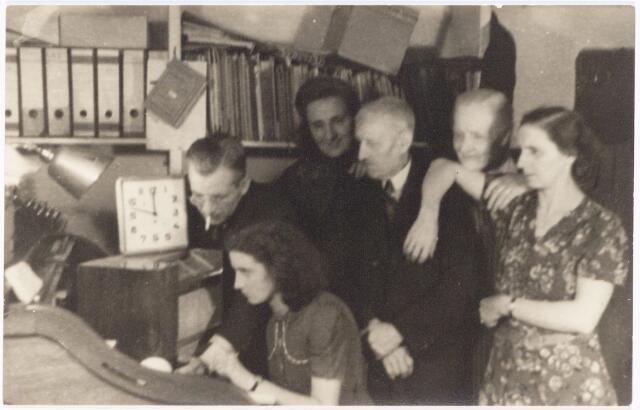 """049841 - """"De luistervinken"""" in het kantoor van De Vet aan de Poststraat. Aan de radio de oudste dochter van De Ven. Boven de radio haar vader. Vervolgens mevrouw R. Zijlmans, de heer en mevrouw Basters en mevrouw De Vet.De foto is een reconstructie van de situatie tijdens de Tweede Wereldoorlog."""