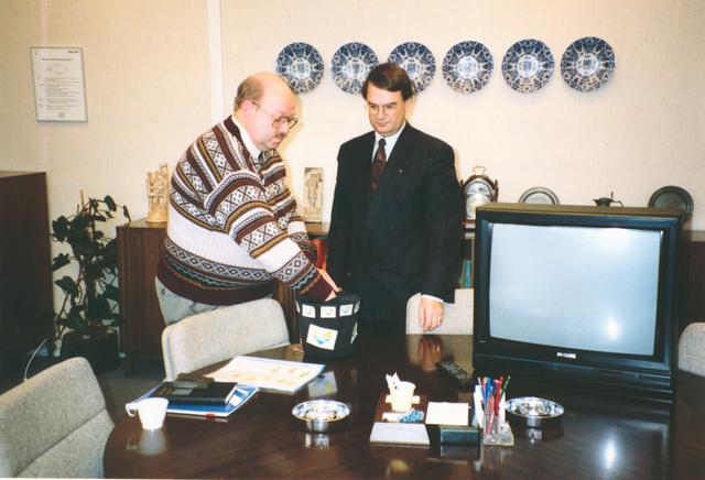 651489 - VOLT, Tilburg. Noord. Begin januari 1992 werd een z.g.n. customerday wereldwijd in elke  Philipsvestiging gehouden. Hiervoor werden bij Volt 20 televisie toestellen gebruikt. Deze toestellen werden onder de nieuwprijs verkocht. Er waren 100 liefhebbers, vandaar dat een loting werd toegepast. Links de heer Rombouts, voorzitter van de ondernemingsraad en rechts de heer Daniels, destijds directeur van Volt. De wandborden op de achtergrond zijn het cadeau van de Philips- bedrijven in de 6 provincies waar ze gevestigd waren tijdens het 40 jarig jubileum van Volt in 1949.
