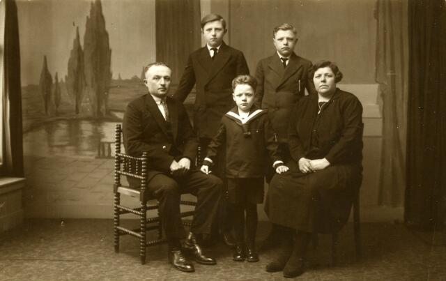 093082 - Het gezin Coppens-Sillius. Wever Adrianus Henricus (Janus) Coppens werd geboren te Goirle op 31 januari 1894 als zoon van Johannes Cornelis Coppens en Johanna van Gool. Hij trouwde in Veendam op 18 september 1915 met Tammechien Sillius, geboren aldaar op 6 maart 1896. Hij gezin woonde aanvankelijk in Muntendam, maar verhuisde al snel naar Goirle, waar Janus Coppens als linnenwever de kost verdiende en Tammechien zich bekeerde tot het katholieke geloof. Zij woonden daar aan de St. Jansstraat 48, maar verhuisden in 1938 naar de Korvel Dwarsstraat in Tilburg. Later is het echtpaar gescheiden. Janus sleet zijn laatste jaren in bejaardencentrum Ten Bijgaerde te Oisterwijk, waar hij ook begraven werd. Hij overleed in Tilburg op 22 maart 1972. Tammechien Sillius overleed te Hilvarenbeek, waar zij woonde in een bijbouw bij de familie Horrevorts, op 15 februari 1972. Op de foto op de eerste rij v.l.n.r. Janus Coppens, zoon Antonius Johannes Adrianus Catharina (Toon) Coppens, geboren te Goirle op 19 september 1933, woonachtig te Tilburg kwam hij als oorlogsslachtoffer te 's-Hertogenbosch op 16 september 1944 om het leven, en Tammechien Sillius. Op de achtergrond links Johannes Hermannus (Jan) Coppens, geboren te Muntendam op 13 september 1916 en overleden te Tilburg op 10 januari 1982. Hij trouwde met Maria Elisabeth van Beers. Rechts Joseph(i)us Johannes Maria Coppens, geboren te Goirle op 31 oktober 1923, kwam tijdens de Tweede Wereldoorlog waarschijnlijk in Rusland om het leven. Verder waren er nog twee zonen: Jan Joseph Maria Coppens, geboren te Goirle op 19 april 1921 en daar reeds na enkele maanden, op 17 augustus 1921, overleden, en Johannes Cornelis Coppens. Hij was als onwettige zoon van Tammechien Sillius geboren te Veendam op 6 april 1915, maar werd bij het huwelijk van zijn ouders gewettigd. Hij was katoenwever van beroep en verhuisde reeds een jaar voor zijn ouders, in 1937, naar Tilburg. In 1938 ging hij niet bij zijn ouders wonen, maar verhuisde hij na