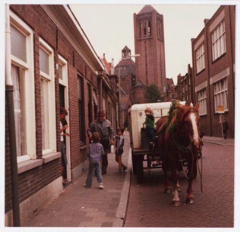 """034111 - Melkhandelaar annex """"boer"""" J.A.C.de Brouwer had zijn zuivelwinkel aan de Voltstraat 34 pal naast het oude hoofdkantoor van Volt (Voltstraat 32). Hij heeft zijn melktoer altijd gereden met paard en wagen zoals hier op de foto van september 1968. Kennelijk werd hij toen 65 jaar en nam hij toen afscheid van zijn klanten. Ook het paard deelde mee in de feestvreugde. Aan de """"haam"""" hangen diverse bossen worteltjes. Jan de Brouwer loopt hier met enkele flessen melk naar Mw. van Diesen? op huisnr. 31 aan die Voltstraat, die met de portemonnee gereed staat. Rechts achter de bushalte gebouw B van Volt met toen beneden de ontwerpgroep condensatoren en de bijbehorende tekenkamer en proevenwerkplaats. Boven was de grote kantine. Helemaal achteraan de kerk van Broekhoven I gebouwd door architect J. v.d. Valk."""