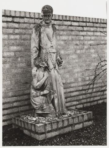 """067997 - PETRUS DONDERS, beeldhouwwerk uit ca. 1923 van P.J.L. CUSTERS (1867-1942). Lokatie: kerkhof van de parochie Heikant. Petrus Norbertus (""""Peerke"""") DONDERS (Tilburg 27 okt.1809 - Batavia, in Suriname, 14 jan.1887), missionaris, afkomstig uit een zeer arm milieu, ging op 22-jarige leeftijd naar het klein seminarie te St. Michielsgestel en werd in 1841 priester gewijd. In 1842 vertrok hij naar Suriname en ik 1856 vestigde hij zich als pastoor te Batavia aldaar, het toenmalige leprozenetablissement aan de Coppenamerivier. Donders verzorgde de zieken met de grootste toewijding en leeft in Suriname voort als de 'vader der melaatsen', als 'vriend van de bosnegers (gevluchte slaven) en 'apostel der indianen'. Toen in 1866 de Surinaamse missie aan de redemptoristen werd toevertrouwd, trad hij tot deze congregatie toe. Hij heeft 44 jaar in Suriname gewerkt. In 1913 werd het proces van zijn zaligverklaring ingeleid. Op 23 mei 1982 kondigde paus Johannes Paulus II de zaligverklaring af. Petrus Donders ligt begraven in de kathedraal van Suriname. Op zijn geboortegrond aan de Heikant in Tilburg is al zo'n eeuw geleden een bedevaartplaats ontstaan.   Religieuze kunst, openbare ruimte"""