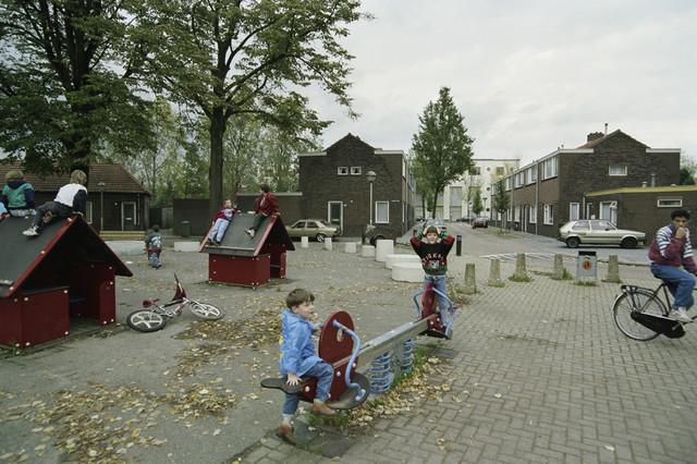 TLB023000261_004 - Speeltuin met speeltoestellen en spelende kinderen op een plein. Foto genomen in richting Ringbaan Oost. Foto is gemaakt in het kader van de Gemeentelijke Begrotingsspecial 1993 waarin aandacht werd geschonken aan  stadsvernieuwing en wijkaanpassingen.