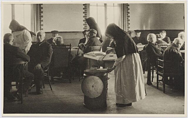 012289 - WO2 ; WOII ; Tweede Wereldoorlog. Evacuatie. Etenstijd voor bejaarde evacués uit de Betuwe in de Leo XIII-school. De zusters Franciscanessen kregen bij hun werkzaamheden hulp vanuit de jeugdbeweging, met name de verkennerij
