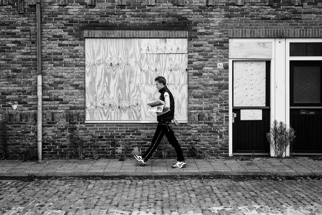 digi 1692_005 - Huis-aan-huis krantjes rondbrengen in de wijk die in de volksmond bekend staat als de 'Vogeltjesbuurt'. De huizen zijn dichtgetimmerd vanwege een renovatie of nieuwbouw. De foto is onderdeel van een fotoserie van Anja van Eersel. Volksbuurt. Broekhoven. Groenewoud.