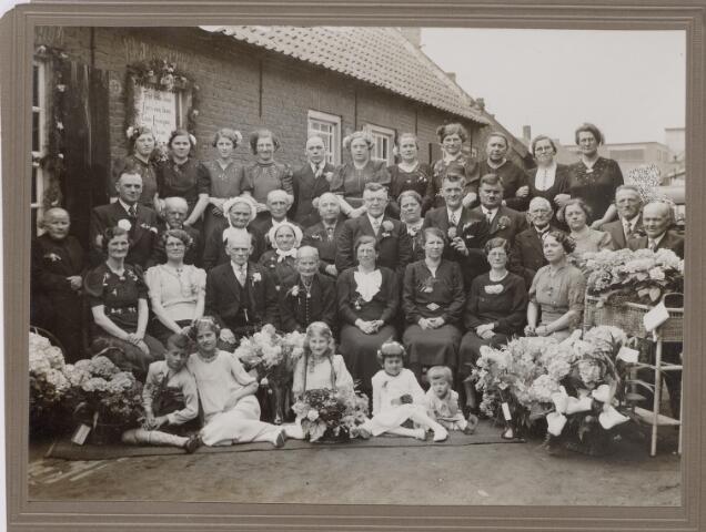 043835 - Aan de Vernisstraat 53 (huidige Surinamestraat) vierden Cornelus Laurijssen, wolwasser geboren te Tilburg op 5-5-1867 en Maria Catherina van Puijfelik geboren te Tilburg 22-6-1862 hun gouden bruiloft. Zij trouwden in Tilburg op 2-5-1889.  Kees en Mieke staan afgebeeld op een sigarenbandje.Dit was vroeger tamelijk gangbaar.Kees werkte als wolwasser bij Jan Pessers aan de van Bylandtstraat. Zittend op de voorgrond met pijpekrullen kleindochter Tony Weijters.Vlak achter het gouden bruidspaar staat (met muts) Betje Laurijssen, zij was voorbidster in de Hasseltse kapel.Links achter haar met muts staat Marie Laurijssen. Helemaal rechts achteraan Annie Neve-Spijkers (kokkin op de bruiloft).Tweede vrouw rechts van de gouden bruid schoondochter Marie Damen.Staande achter haar,met sigaar, haar man Willem Laurijssen.Rechts van de gouden bruid, dochter Mieke Laurijssen achter haar haar man, Toon van Loon oudoom van Noud van Loon (fietsenspeciaalzaak)