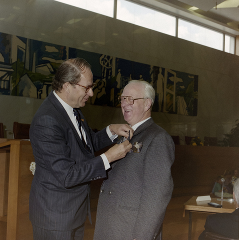 1237_012_970-1_009 - Koninklijke onderscheiding. Lintje. Lintjesregen bij de Gemeente Tilburg in april 1992. Burgemeester Gerrit Brokx spelt een lintje op in de vergaderzaal van Gemeente Tilburg.