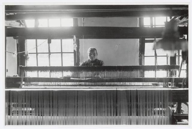 037464 - Textiel. Vrouw achter een weefgetouw omstreeks 1920. In die tijd werd thuisweven vaak ook nog beoefend als een welkome bijverdienste