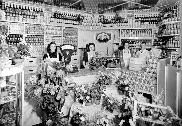 650537 - Schmidlin. Kruidenierswinkel J.A. van de Wiel aan de Hoefstraat, september 1948. Van links naar rechts Sjannie Spijkers, Sjaantje Smulders, Annie van de Wiel en Jan  van de Wiel. Op de foto midden achter Jos en Truike van de Wiel ( de ouders van Jan).