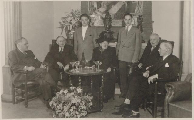 045046 - De wollendekenfabriek van de firma Pessers-van Zuylen stond aan de Kuiperstraat. In 1935 werd het bedrijf uitgebreid met een kamgarenspinnerij aan de Goirkekanaaldijk. Op de foto twee jubilerende werknemers: Janus Janssen en Jan van Huijkelom. Zittend v.l.n.r. directeur Jan Pessers, Janus Janssen, Adriana J.M. Spijkers, haar man Jan van Huijkelom en directeur Harrie Pessers. Staande Hans Beekman en A. van Berkel.