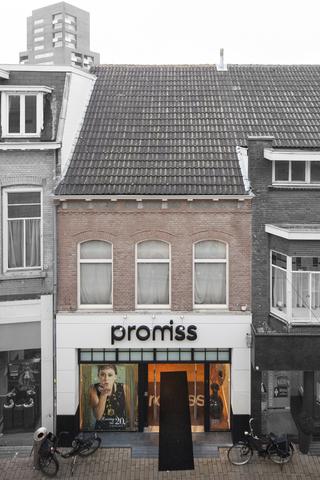 1611_019 - Heuvelstraat in Beeld. Dit pand heeft in 1982 in de oude stijl een nieuwe bovenzijde gekregen, daarbij zijn schrale stenen gebruikt.De omlijsting van de etalage is hoog opgetrokken.  In dit pand hebben diverse ondernemers gezeten waarvan Elzerman verlichting en huishoudelijke artikelen en Singer Mij. NV de bekendste zijn