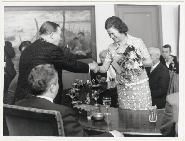 90591 - Made en Drimmelen. Mw. Bets van de Westen wordt gefeliciteerd door burgemeester Smits tijdens de viering van haar 25 jarig jubileum als telefoniste op het gemeentehuis in Made.