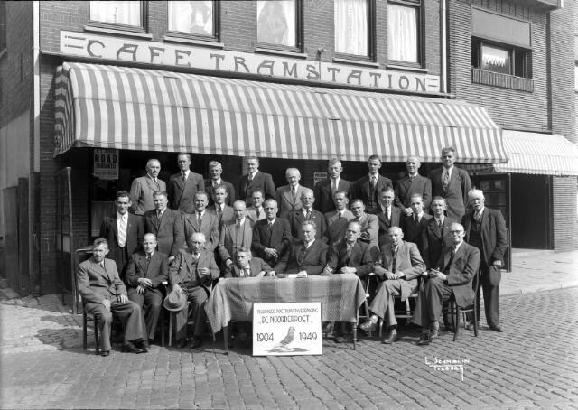 """650499 - Schmidlin. De postduivenvereniging Noorderpost gefotografeerd ter gelegenheid van het 45-jarig bestaan voor het café Tramstation aan het Wilhelminapark, 1948.  Postduivenvereniging """"De Noorderpost"""". De jubilerende postduivenvereniging """" De Noorderpost"""" (1904-1949) die het café als thuisbasis had. Vanwege de oorlog werd het 40 jarig jubileum niet gevierd. """"De Noorderpost"""" was van oorsprong een Hasseltse vereniging opgericht in 1904 (publicatie 06-10-1904 T.C.). De vereniging was  aanvankelijk gevestigd in café Kerkzicht in de Hasseltstraat . Later werd een nieuwe thuisbasis gevonden aan het Wilhelminapark. Diverse leden woonden in de Hasselt. Links zittend achter de tafel is Noud van Berkel uit de Hasseltstraat. Staande achter de tafel met handen op zijn buik en sigaret in de hand is Kees Bertens getrouwd met Fien Zebregs, dochter van de kastelein. Links op de bovenste rij staat Jac Zebregs, eigenaar van café Tramstation. Bovenste rij, derde van links, Frans de Cock."""