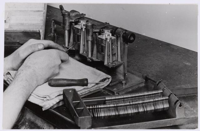 038997 - Volt. Zuid. Fabricage. Productie. Condensatoren. Ca. 1955. Bewerking: het uittrekken van vulplaten uit condensatoren. De vulplaten werden gebruikt als hulpmiddel om de zuivere afstand tussen rotor- en statorplaten te bewaren tijdens het solderen van de rotor- en statorpakketten alsmede tot na het bevestigen in de uiteidelijke eindconstructie. Locatie gebouw C.