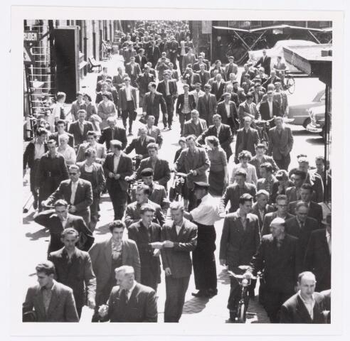 """039139 - Volt. Zuid. Algemeen.Groepsfoto. """"Uitgaan"""" van de Volt tijdens de middagpauze bij de poort aan de Voltstraat. Dat was in 1959 nog de hoofdingang. De middagpauze voor het fabricagepersoneel was toen anderhalf uur, van 12.00 tot 13.30 uur."""