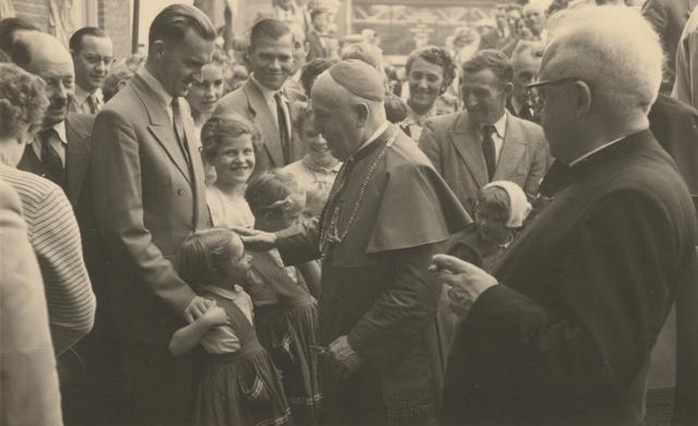 653322 - Parochie Gasthuisring. Na de wijding van de nieuwe kerk O.L.Vrouw van Altijddurende Bijstand zegent bisschop Mgr. W. Mutsaerts de kinderen.
