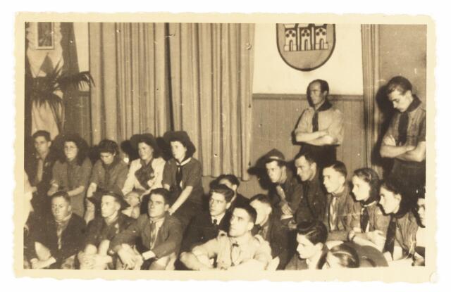 052902 - Jeugdorganisaties. Scouting. Verkennerij na de tweede wereldoorlog in Tilburg; een gezellige avond; voorste rij v.l.n.r. A. Nouwens, K de Gouw, G.v. Grinsvan; op de achtergrond mej de Beer en mej. N. de Jong