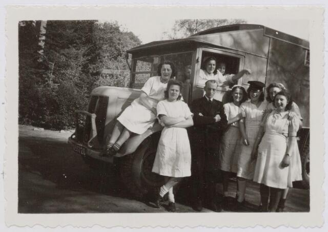 046357 - Medisch kinderdagverblijf Kleuterheil. Verplegend personeel bij de auto die na de bevrijding gebruikt werd voor het vervoer van de kinderen.