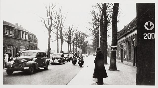 012762 - Tweede Wereldoorlog. Bevrijding. Een geallieerde colonne op de Bredaseweg nadert de kruising met de Ringbaan-West. Het bewegwijzeringsbord op de boom links geeft de route bnaar het vliegveld Gilze-Rijeen aan. Het bord op de boom rechts bepaalt de richting van de troepenverplaatsing