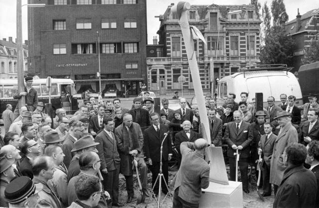 065814 - Op de jaarlijkse persdag in Tilburg hebben journalisten, die deze dag bijwoonden, de eerste spade gestoken voor de bouw van een nieuw station in Tilburg. De plechtigheid werd afgesloten met het plaatsen van een 'monument', een reusachtige schep op de plaats waar het nieuw station zou worden gebouwd. Ook de burgemeester, C.J.G. Becht, toonde zijn belangstelling.