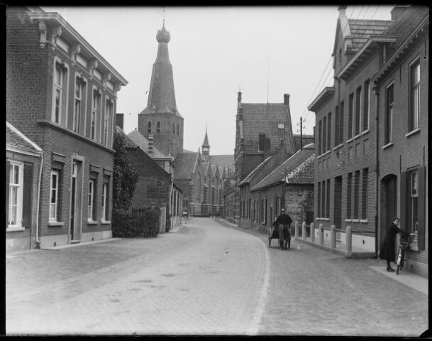 500393 - De Kerkstraat met de zestiende-eeuwse St Remigiuskerk, welke van oudsher tot in 1860 de parochiekerk van beide Baarles was. Tijdens de bevrijding van het dorp door militairen van de 1e Poolse devisie raakte de kerk op 2 oktober 1945 verbrand, waarschijnlijk door uitgeworpen fosforbommen.