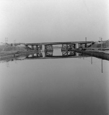 1232_16_261 - Tilburgse koerier. Station Tilburg in aanbouw.  Centrum Tilburg. Brug kanaal in aanbouw. Ouder echtpaar