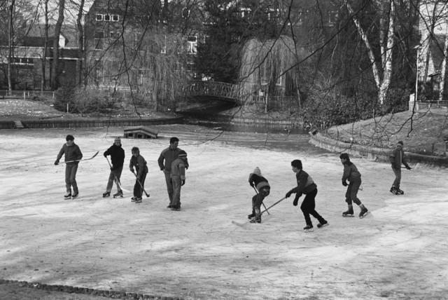 TLB023002433_002 - Op een bevroren vijver ijshockeyschaatsen in het Wilhelminapark te Tilburg